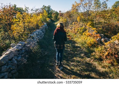 Girl walking on a path when autumn leaves