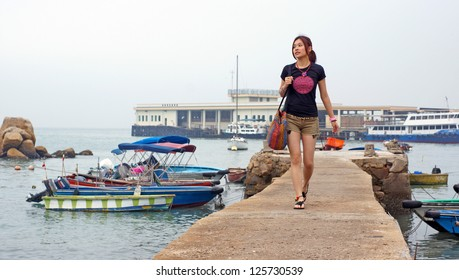 girl walking on the pier with the sea background ,nature style in hong kong Lamma Island countryside