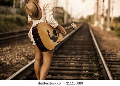 Girl walking on railway wish guitar