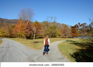 Girl walking on the road, beautiful autumn October day.