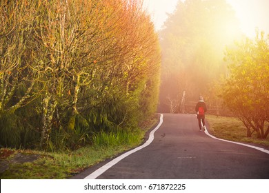 girl walking on the road in foggy with sunshine in the park