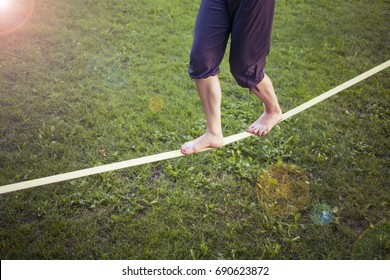 Girl walking on slackline in the park. Balance training