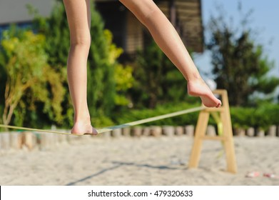 Girl walking on the sling. Child balancing on slackline at a beach. Shadow of a human figures on the sand. Girl is balancing on one leg.