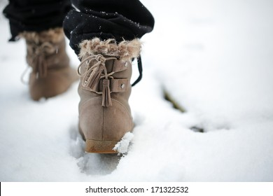 Girl walking on the snow with boots in the afternoon