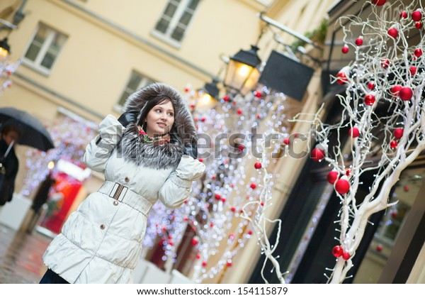 Girl walking on a street decorated for Christmas