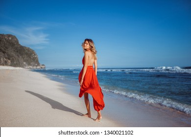 Girl walking on the white sand on the beach.