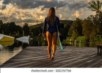 girl walking on wooden path, sport motivation image, water sport photography, wakeboard model on the catwalk