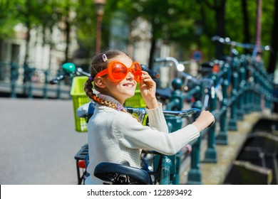 Girl walking in orange glasses for Dutch Queensday on the Amsterdam street