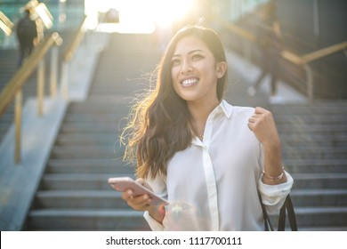 Girl walking in the streer, checking her phone