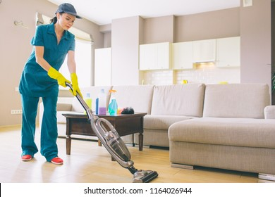 Girl is walking in studio apartment and cleaning floor with vacuum cleaner. She holds it with both hands. Woman is alone.