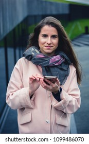 Girl walking and texting on a smartphone outdoors wearing a coat