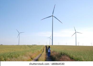 A girl walking through farmland and observing wind turbines