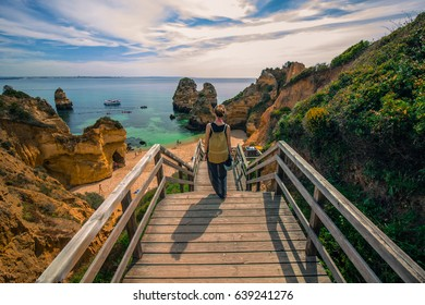Girl walking towards Camillo beach in Lagos, Algarve on the wooden stairs