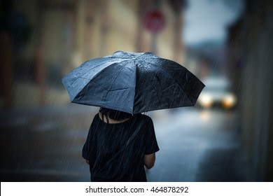 Girl walking with umbrella on rainy day