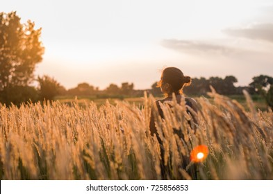 the girl walks across the field. sunset time , a long skirt. whirl with camera in hand, joy