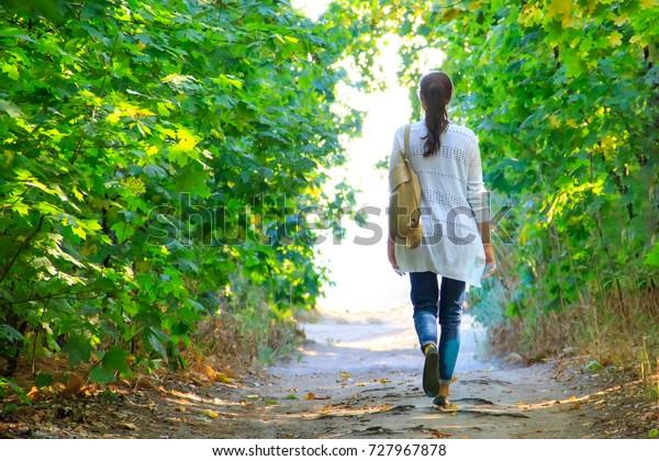 Das Mädchen geht den Weg im Wald entlang bis zum Licht in einer weißen Jacke und Jeans.