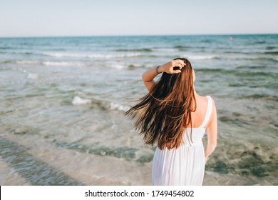 girl walks along the sea. back view. A woman alone on the sea shore admires the evening landscape