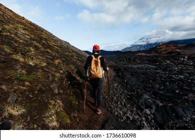 A girl walks along a solidified lava field at the foot of a volcano