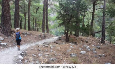 A girl walks along the trail crossing the Samaria Gorge National Park in the island of Crete