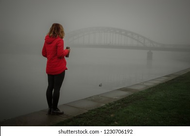 A girl walks in autumn along the embankment, a bridge in the fog, foggy weather, a cup in her hands