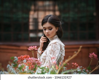 A girl walks in a flowering garden, she has a vintage blouse with a bow, chestnut long hair. she gently cares for her flowers. Sweetheart gardener. Artistic photography. Love of plants.