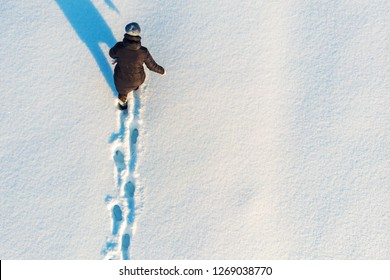 Girl walks or goes in snow leaving footprints, top aerial view. Winter outdoor activity background with copy space