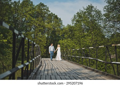 The girl walks with the guy on the bridge.