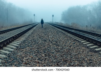 the girl walks on rails in the fog. waiting for the train, a teenager wanders