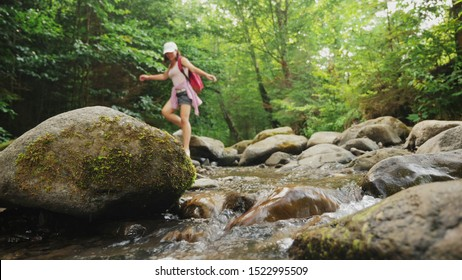 A girl walks on stones along a mountain river in a forest. Legs of young woman stepping over rocks on nature during travel. Low angle of view