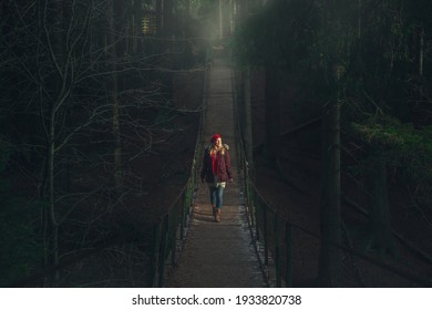 The girl walks on a suspension bridge over a mountain river. Dark, mystical forest.