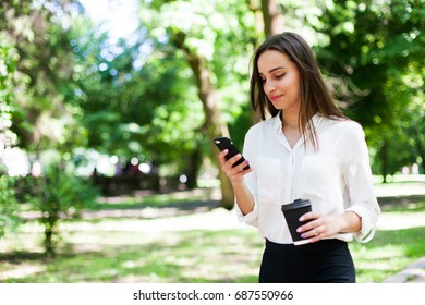 Girl walks with phone in her hand and a cup of coffee in the park