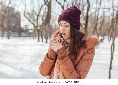 The girl walks in the snow-covered park. On the street the sun shines. The girl looks somewhere in a distance. She has very sensitive look. She very beautifully looks.
