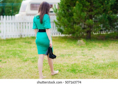 The girl walks in the spring barefoot on a grass