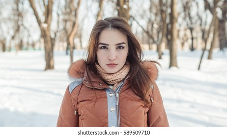 The girl walks in the winter park. She very beautifully looks. Her stare looks directly at us. Hair of the girl have beautifully fallen on shoulders and wind develops them a little.