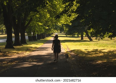 Girl wallking on a street looking as a trees tunnel in Uzvaras Victory Park from Riga, the capital city of Latvia, European baltic country
