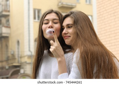 Girl wants to burst bubble of chewing gum. They both have long brown hair that is long to the waist and they are dressed in identical white sweaters.