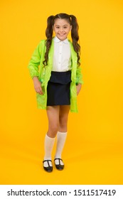 Girl wants it to rain. Happy girl back to school in autumn. Cute little girl smiling on yellow background. Adorable small girl with long brunette hair wearing rain coat for rainy weather.