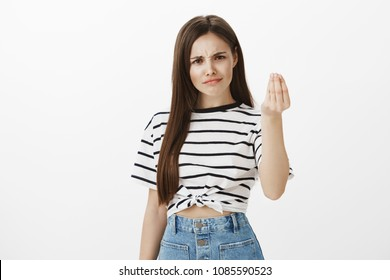 Girl wants tiny act of respect. Unsatisfied questioned european woman with brown hair, frowning from disappointment, raising hand and showing italian gesture what do you want over white wall
