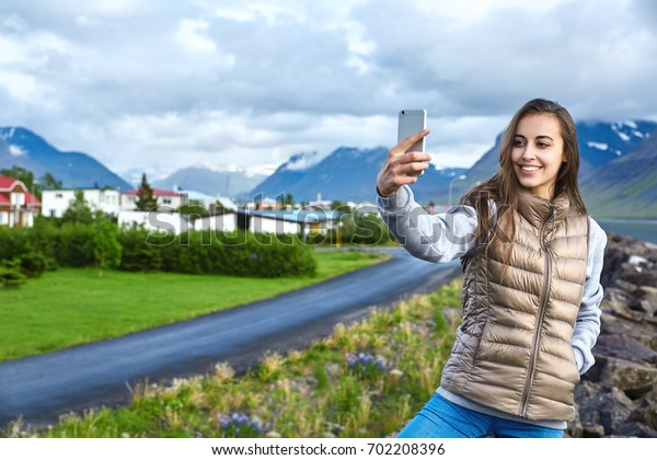 Girl in warm clothing makes selfie photo on background of town and mountains of Iceland. Beautiful summer landscape in Iceland