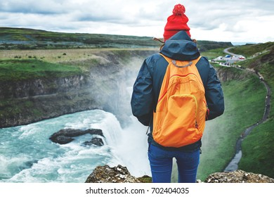 Girl in warm clothing, in red knitted hat and small orange backpack stands on the cliff on background of Gullfoss waterfall in Iceland. Travel to the Iceland