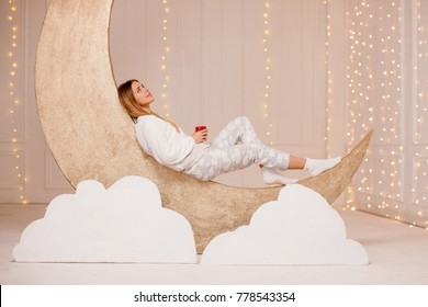 Girl in Warm light Pajamas lying on a Golden Month with a cup of Milk with Honey, Relax Before Going to Bed