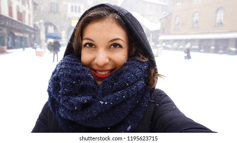 Girl in warm scarf and cap take self portrait in winter snow old town square. Concept winter vacation.