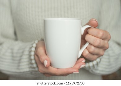 Girl in warm sweater is holding white mug in hands.. Mockup for winter gifts design.