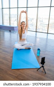 Girl warming up while sitting on yoga mat in front of the camera phone. Female sports blogger records fitness online stream. Home losing weight marathon concept
