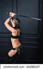 The girl is a warrior in armor and bare waist, she brought the katana over her head. A girl in the tribal style dances with a sword over her head.