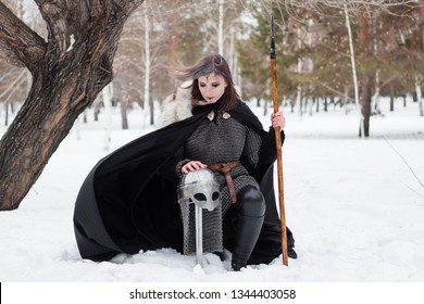The girl is a warrior of the Viking era in a chain mail coat and fur with a spear in his hands. Sits on his knee against the background of a tree and a winter forest.