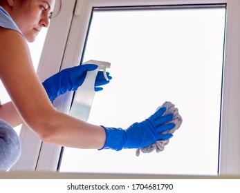 Ein Mädchen wäscht zu Hause die Fenster in Handschuhen.