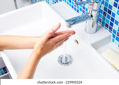 Girl washing her hands with soap in a bathroom sink