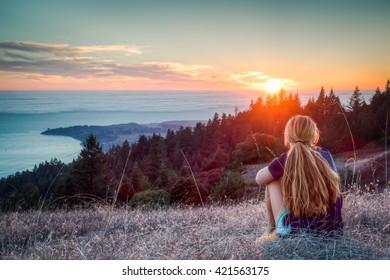 Girl watches sunset above Stinson Beach, CA.