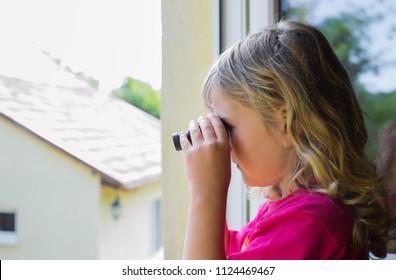The girl watches through binoculars